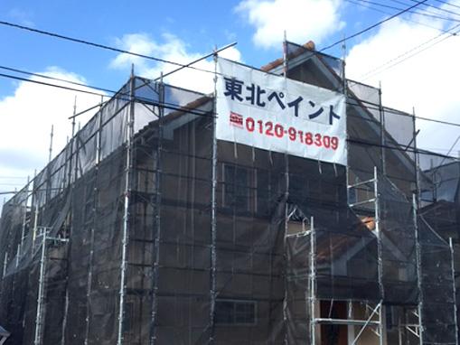 完全にメッシュシートで覆われた塗装中の住宅